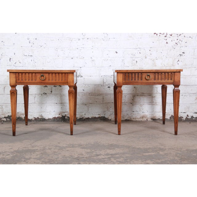 A gorgeous pair of French Regency style side tables or nightstands from the Milling Road line by Baker Furniture. The...