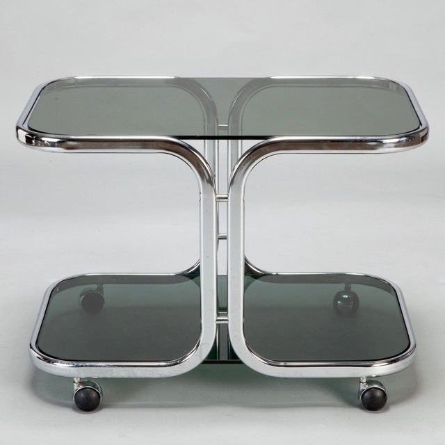 Circa 1960s Italian serving trolley or bar cart has a flat bar chrome frame with two black glass shelves. Chrome cased...