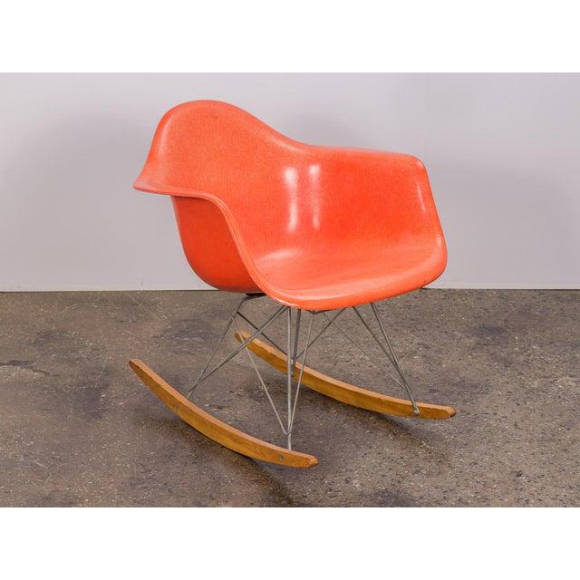 Vintage orange fiberglass armchair shell on a third generation, birch runner rocker base for Herman Miller. Shell is...