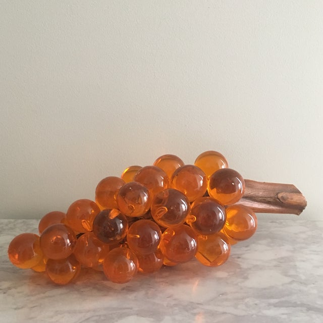 These over sized Lucite grapes with a resin driftwood stem are from the 1960s and would make quite a table centerpiece,...