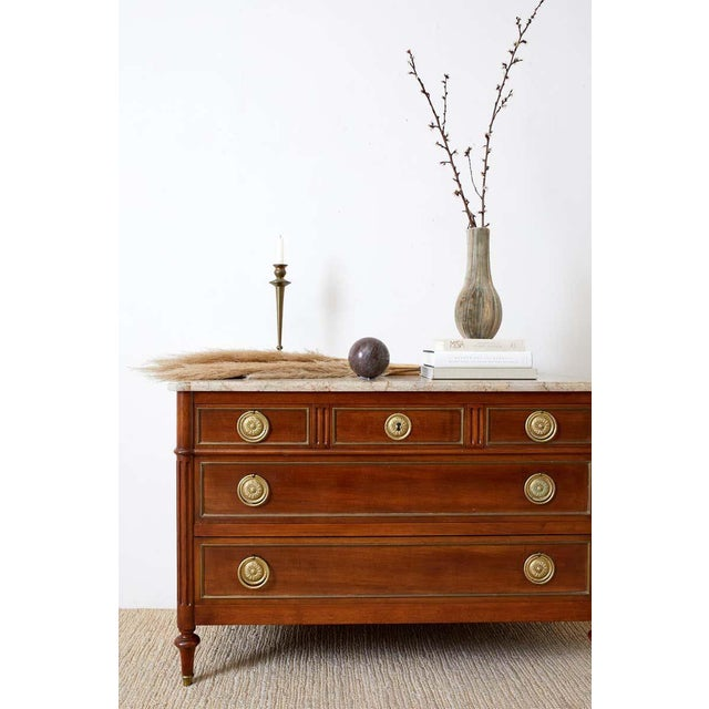 Impressive pair of matching French marble top commodes, chest of drawers, or dressers. Constructed from mahogany each...