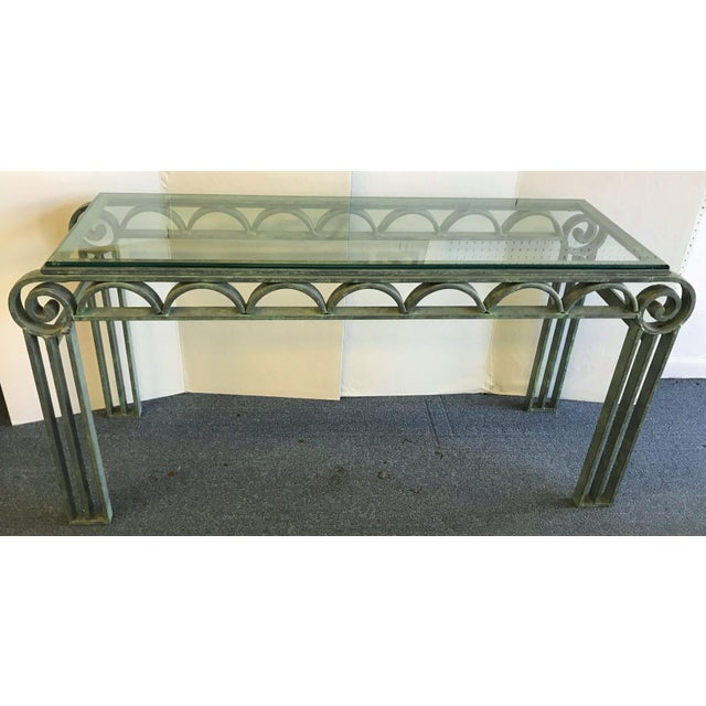 Fantastic iron console table with a beveled glass top. There is an open scroll-like design in a green-grey verdigris...