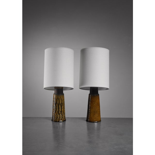 A pair of ceramic table lamps by Kähler. They have a different, but matching mustard yellow glazing with a beautiful...