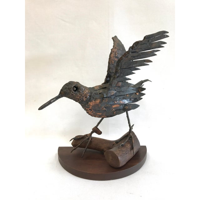 A 1950s copper sandpiper sculpture mounted on a wood branch and base by Herman Fisher. The body is almost brutalist in its...
