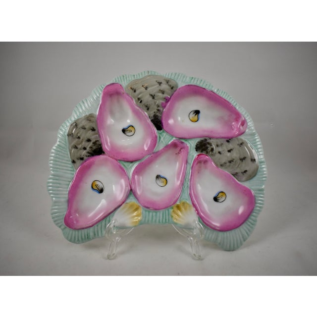 A late 19th Century, French porcelain, crescent shaped oyster plate, five pink lined oyster wells with hand-painted eyes,...