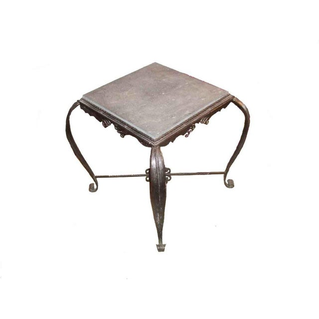 A wonderful handmade iron side table with scrolled feet and decorative stretcher and apron. France, 1930's.