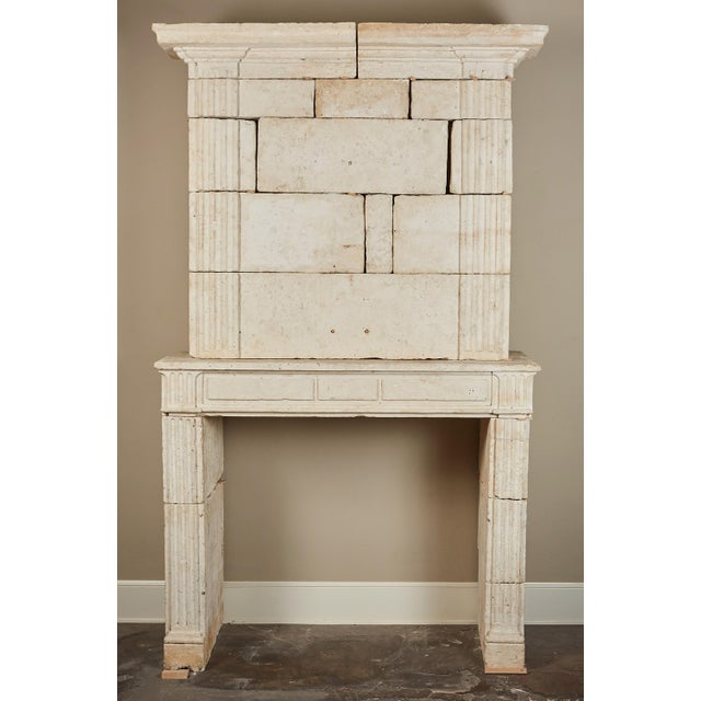 An 18th century French limestone fireplace surround in the Neoclassical style. Of impressive dimensions, the upper section...