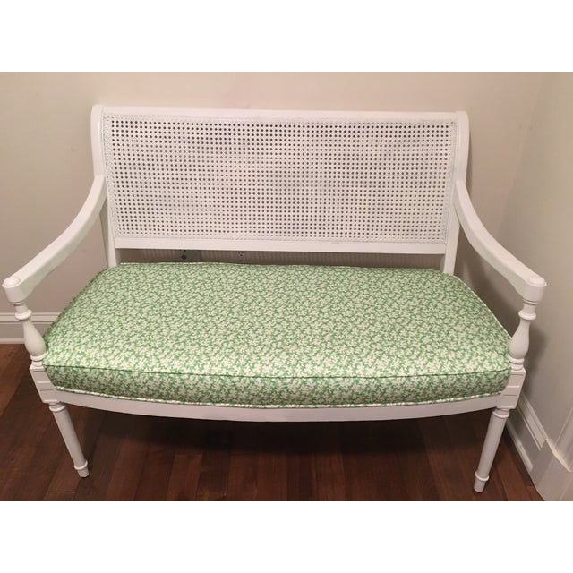 Vintage cane back settee. Newly lacquered in white. Freshly upholstered in Scalamandre fabric (Reef in Jungle) with brand...