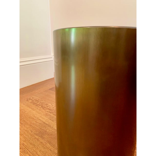 This elegant side table is finished in a smooth gold bronze, and features hidden wheels under the cylinder for practical,...