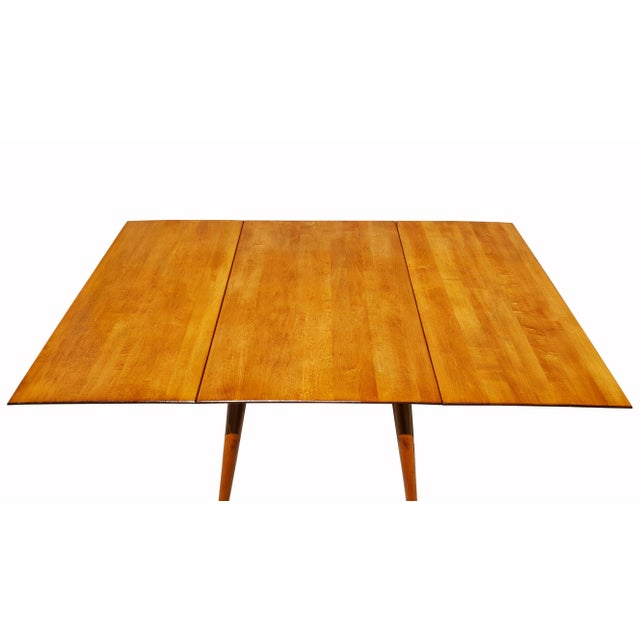 Paul McCobb Planner Group drop-leaf dining table. Made of solid maple. In a tobacco finish. Made in the 1950s.