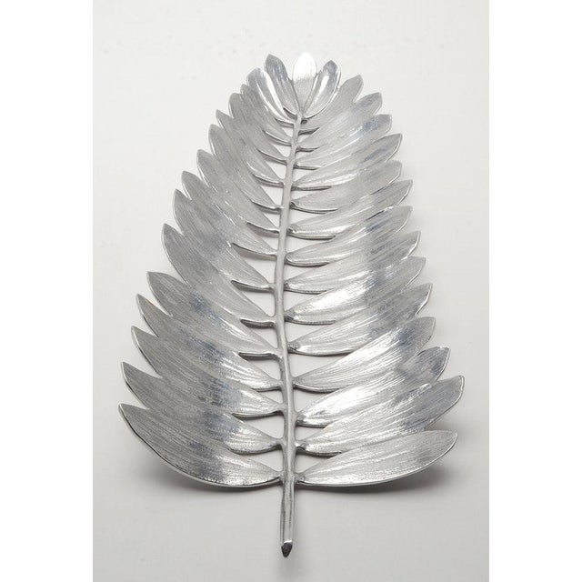 A Michael Aram centerpiece bowl designed in an openwork palm leaf form and made of polished stainless steel. Appropriate...