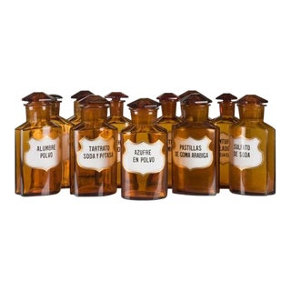 A set of ten amber cut glass bottles each with a stopper and a label identifying the original contents from Spain c. 1900
