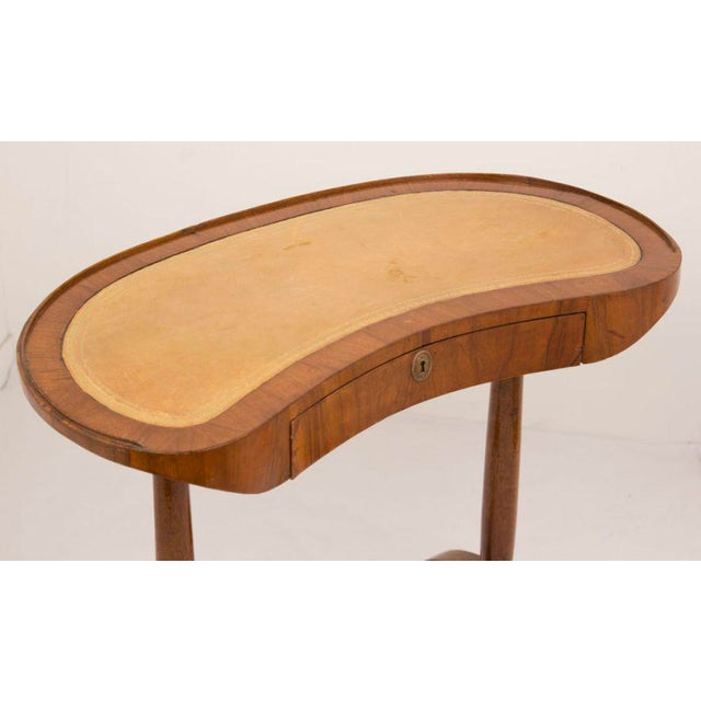 A very nice early 19th century kidney shaped one drawer walnut writing table with camel inset tooled leather. With an...