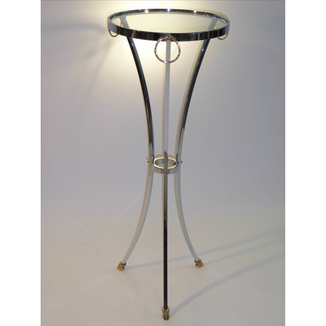 Putting a modernist approach to Empire style, this elegant Maison Jansen pedestal table in chrome with solid brass...