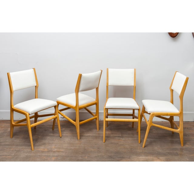 A set of 12 Gio Ponti ashwood dining chairs. Designed by Gio Ponti for Cassina, model 687, design 1953. This set of chairs...