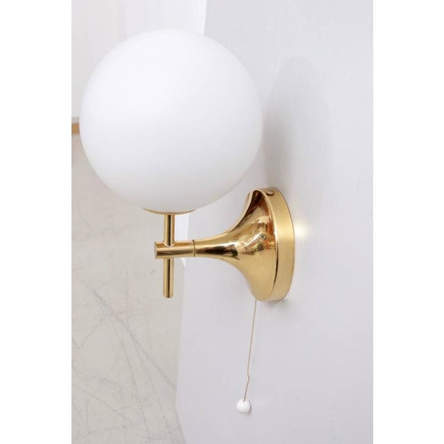 Pair of sconces composed of polished brass golden fixtures with white frosted glass globe shades in excellent condition....
