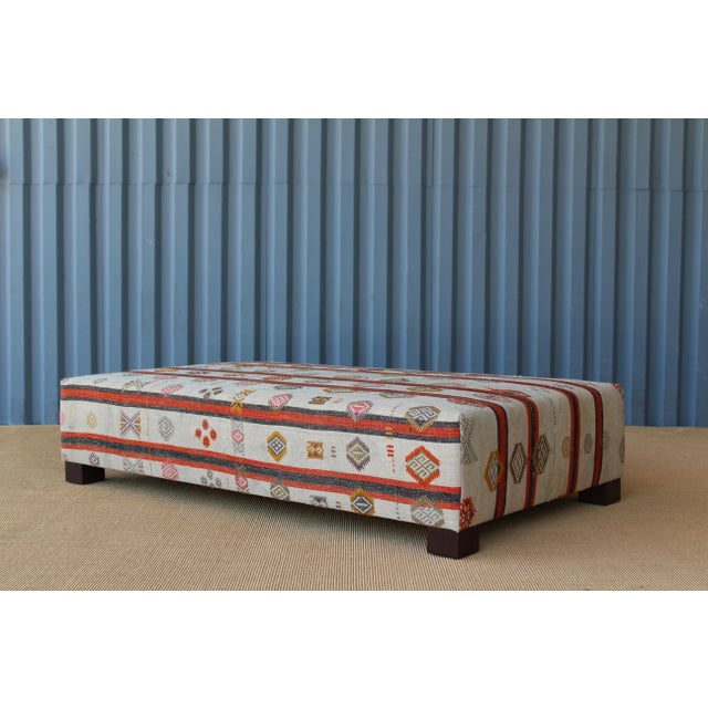 Custom-made ottoman upholstered in a vintage 1950s flat-woven rug. Pops of orange, yellow and pink throughout. Rug has...