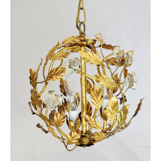 Vintage Italian gold gilt tole three-arm/light ball chandelier with ornate scrolling leaves, scalloped bobeches, and...