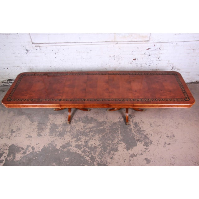 Offering a beautiful 13 foot burled and inlaid Regency style formal extension dining table. This important piece has a...