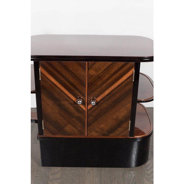 Streamlined Art Deco end table / dry bar cabinet in book-matched exotic Walnut with black lacquer accents and chromed ball...