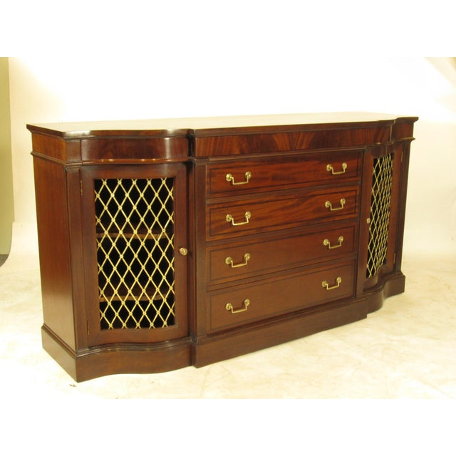 An early 20th century Regency Style inlaid mahogany sideboard with four central graduated drawers flanked by two frieze...
