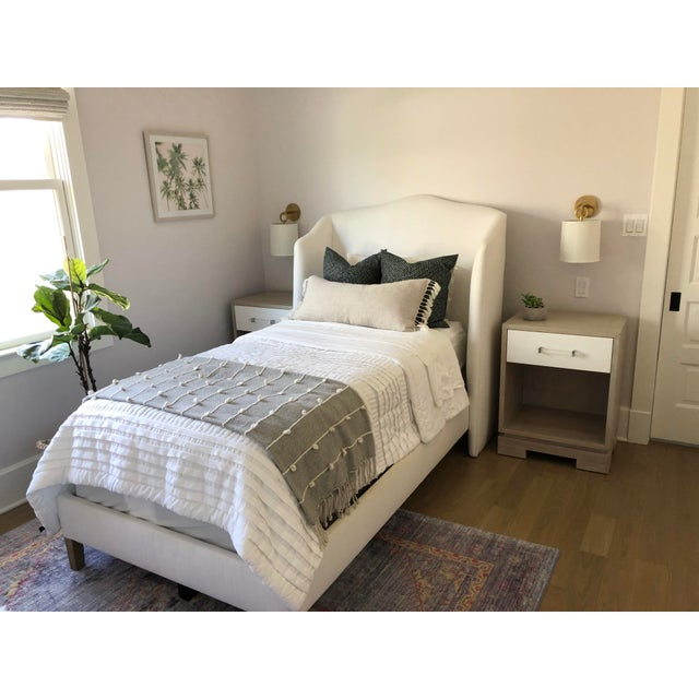 Custom made Gelim White linen upholstered wingback twin bed. White maple wood legs. Purchased through a highly reputable...