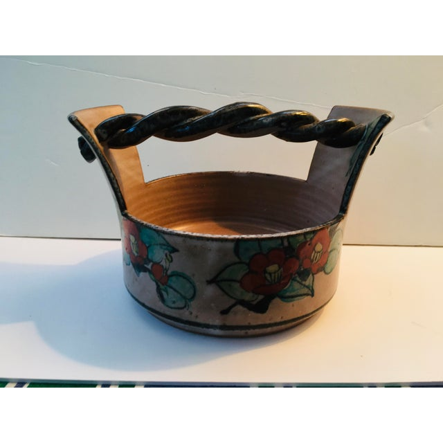 This pottery is all hand made and hand painted. We are guessing it is a serving piece or a container for flower arrangements.