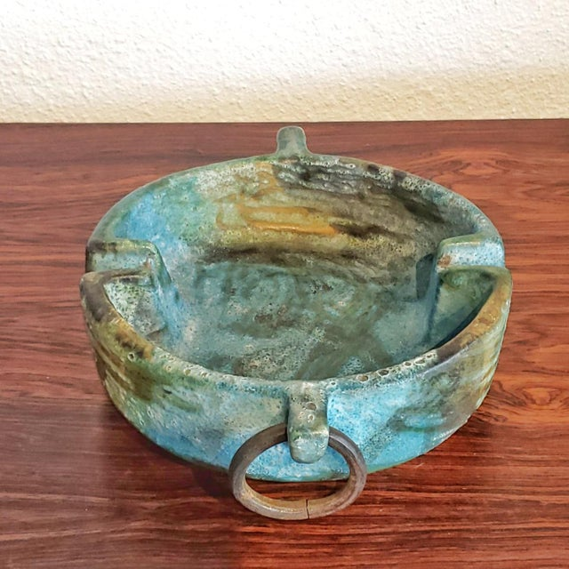 An Alvino Bagni ashtray decorated with iron rings and the famous Sea Garden glaze. ALVINO BAGNI was born in 1919 in Lastra...