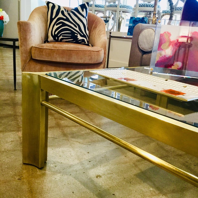 Incredible satin brass coffee table by Mastercraft. A square brass frame with accentuated corners and a glass top, this...