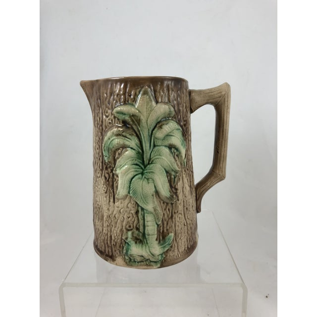 French Majolica pitcher with tree as the focal point and tree bark as the background.