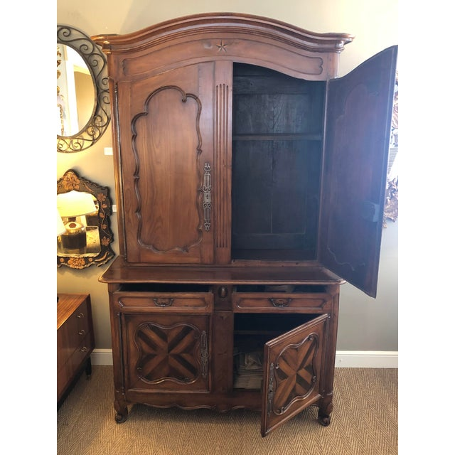 In two pieces, the dramatic arching crest above a 2-door cabinet resting on a base fitted with 2 short drawers over 2...