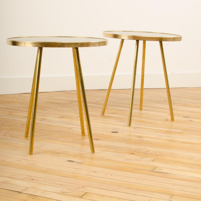 A pair of Italian Modern occasional tables with round black glass tops. Materials: Glass, Bronze/Brass Color: Black, Gold...