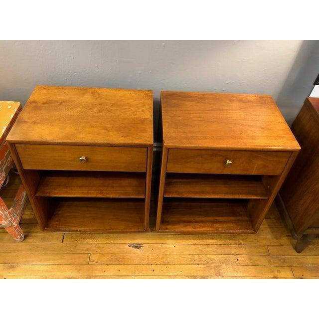 Pair of Drexel Nightstands in walnut from their 'Declaration' line. Brass drawer knobs with walnut veneer inserts....