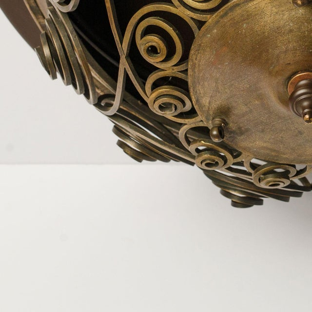 Unique Austrian flush mount light created circa 1920-1940 from cut and hammered brass. Decorated in crossed swirling...