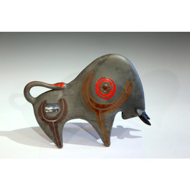 Large vintage Bruno Gambone pottery bull figure in partially abstracted form with repetitive sweeping curves and enameled...