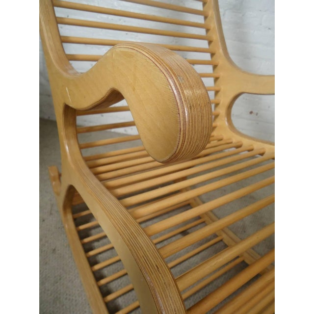 Very large laminated wood rocker with sculpted detailing. Body is made of pressed wood with long dowels comprising the...