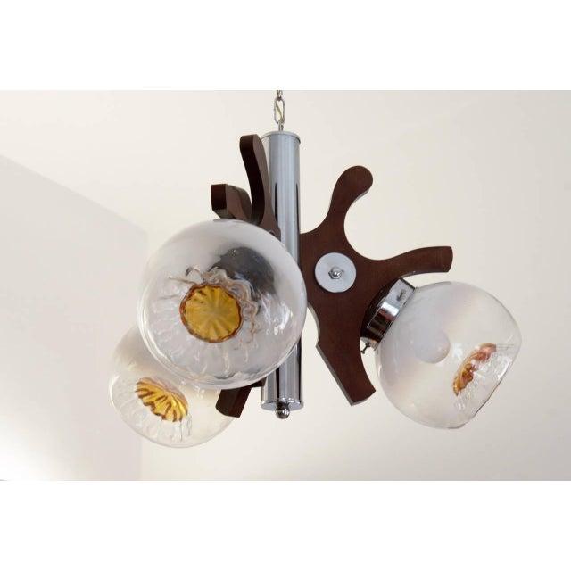 This ceiling lamp was designed and manufactured in the 1970s. It consists of three Murano glass umbrellas and a wooden...