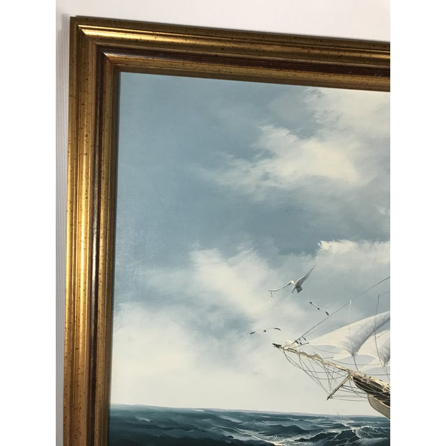 Large oil on canvas painting featuring an American sailing ship at sea. Finished in a gold tone wood frame.