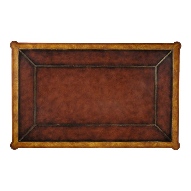 A mahogany and flame okum veneered writing table, the tooled leather inset top with protruding rounded corners above three...