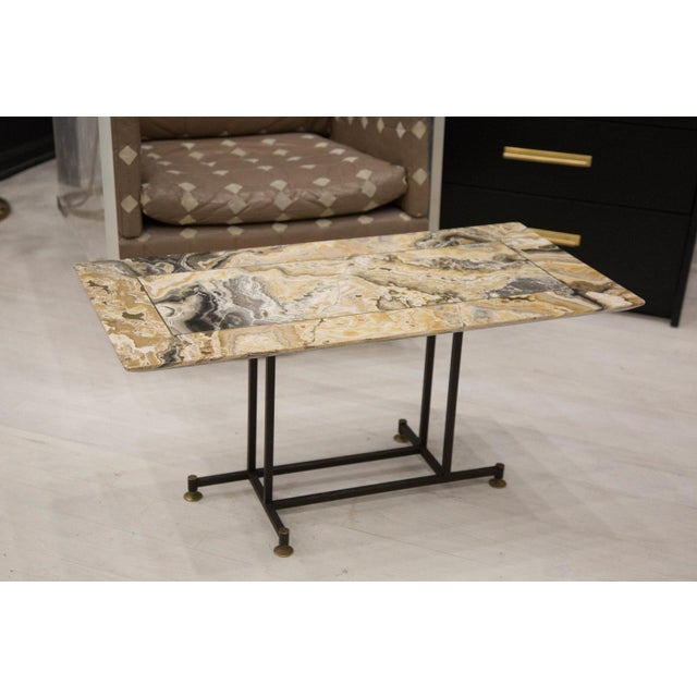 A gorgeous onyx clad table with brass inlay on a black iron frame with brass sabot feet. Condition: Excellent,...