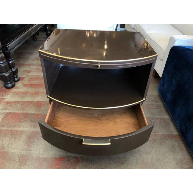 This is a single art deco style nightstand with one drawer and a pull out platform. It has a dark wood lacquer finish and...