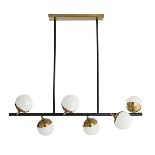 Opal glass spheres have been placed asymmetrically across a bronze bar, giving the chandelier an organic effect...
