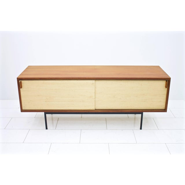 Teak sideboard with seagrass and two sliding doors and black metal base. Dieter Waeckerlin for Behr. Measure: Wide 174cm,...