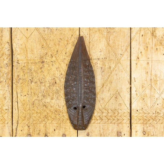 An African mask, uniquely carved in a teardrop shape with intricately carved tribal details and wears a lovely aged...