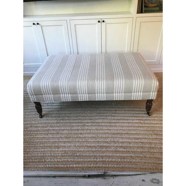 Miles Talbot upholstered ottoman. Can also be used as coffee table. Sand and white striped fabric, brass casters and...