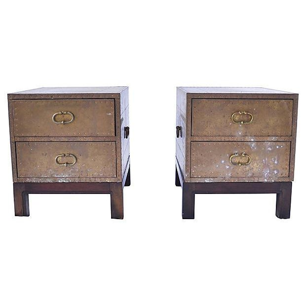 "Set of two 1970's Sarreid-style brass-clad two-drawer chests with separate wood bases. Chests: 16""H; bases: 7.25""H."