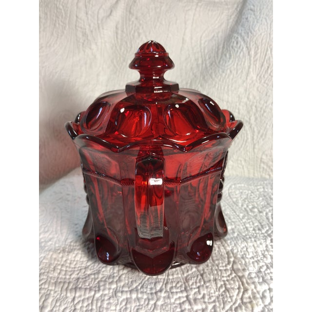 This Spooner Vase was made by Mosser Glass and features embossed cherries on two sides, a scalloped top rim, and...