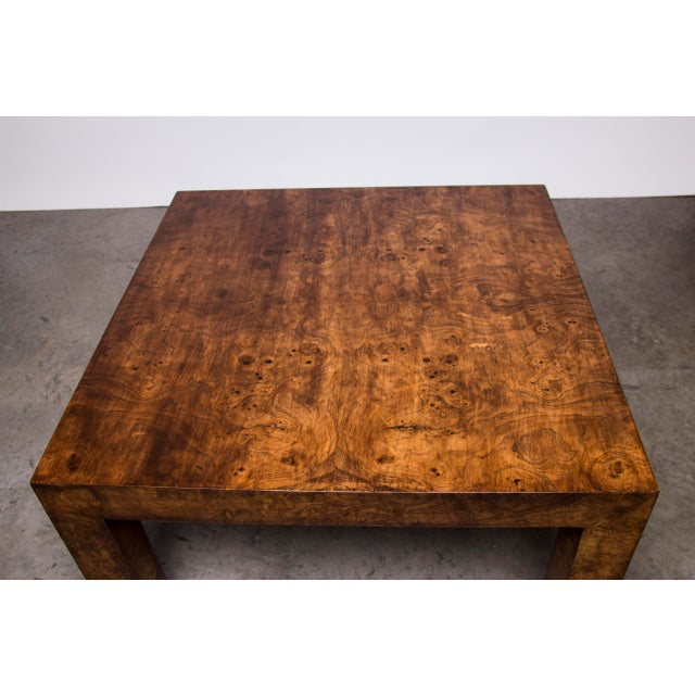 An uncommon and expansive burl coffee table. This rich table features a high quality construction of mirrored burl veneer...