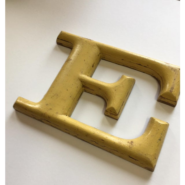 """Yellow orchure colored letter """"E"""". French dated 1940."""