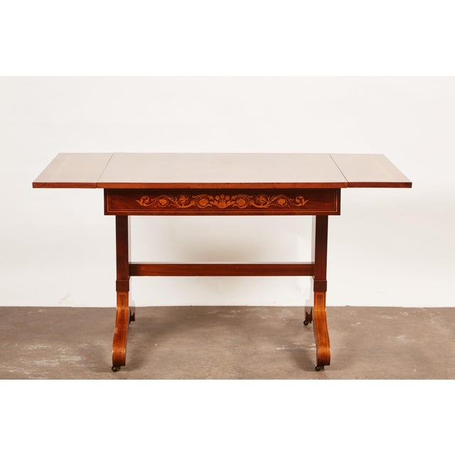 A 19th century Danish mahogany drop leaf table in the style of Empire. The table features wood intarsia inlay of foliage...